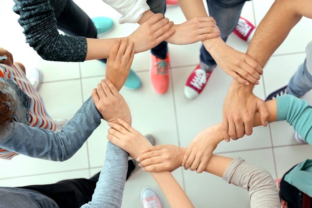Teamwork. Händer bildar en ring.
