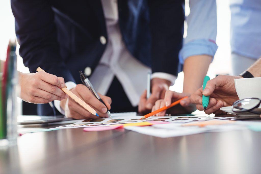 Personer i möte pekar med pennor